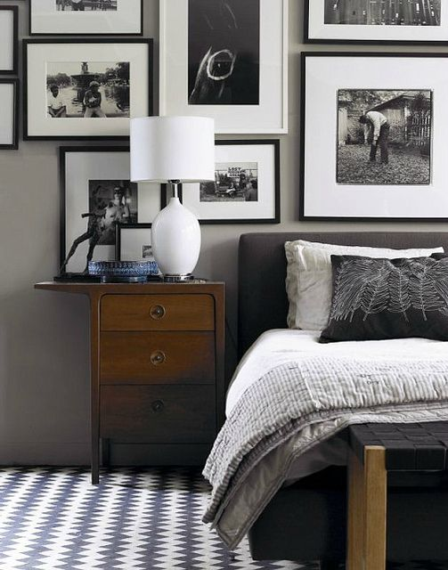 #bedroom collage frame wall with black & white photos, gray & white bedding, patterned area rug, wall color