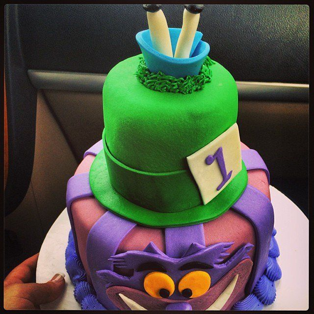 Pin for Later: Make It a Magical Day! 50 Wow-Worthy Disney Cakes A Very Merry Unbirthday The mischievous Cheshire Cat provides the base for your Alice in Wonderland-themed two-tiered cake.  Source: Instagram user chrissybabycakes