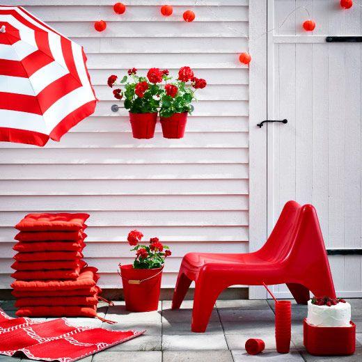 Eine Terrasse mit einem Stapel HÅLLÖ Kissen in Rot, Sessel, Sonnenschirm, Teppich und Blumentöpfen ebenfalls in Rot