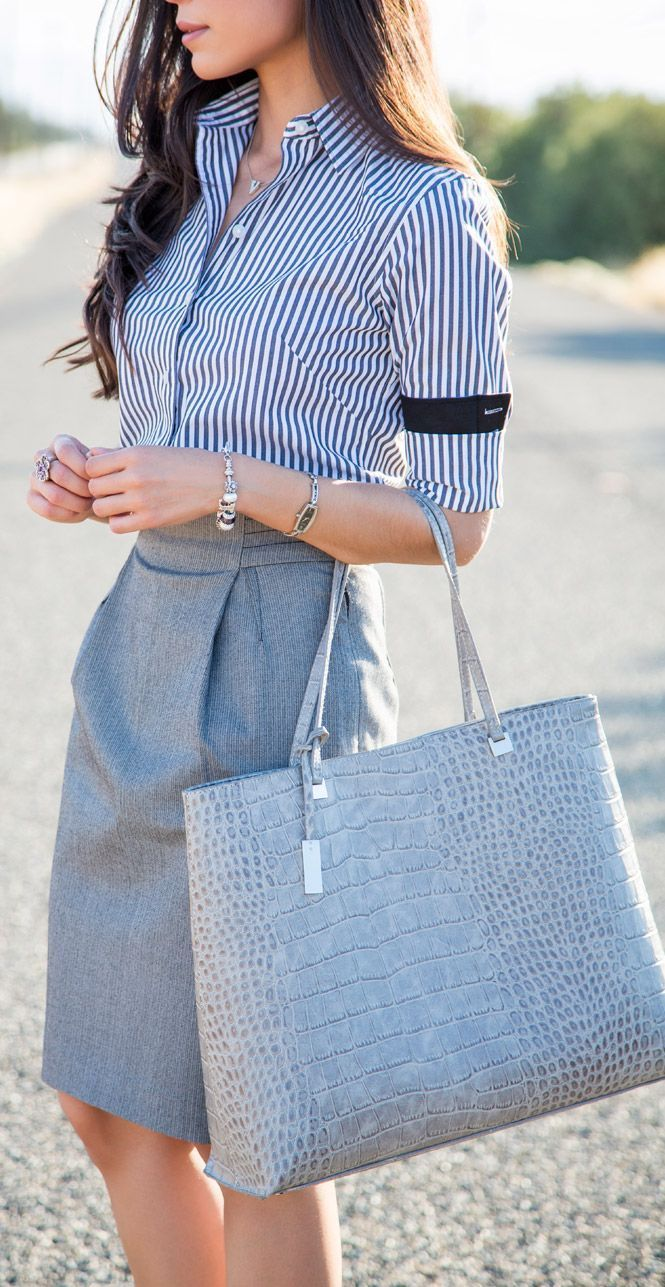Comprar ropa de este look: https://lookastic.es/moda-mujer/looks/camisa-de-vestir-falda-lapiz-bolsa-tote-pulsera-reloj/11529   — Camisa de Vestir de Rayas Verticales en Blanco y Azul Marino  — Pulsera Plateada  — Reloj Plateado  — Falda Lápiz Gris  — Bolsa Tote de Cuero de Serpiente Gris