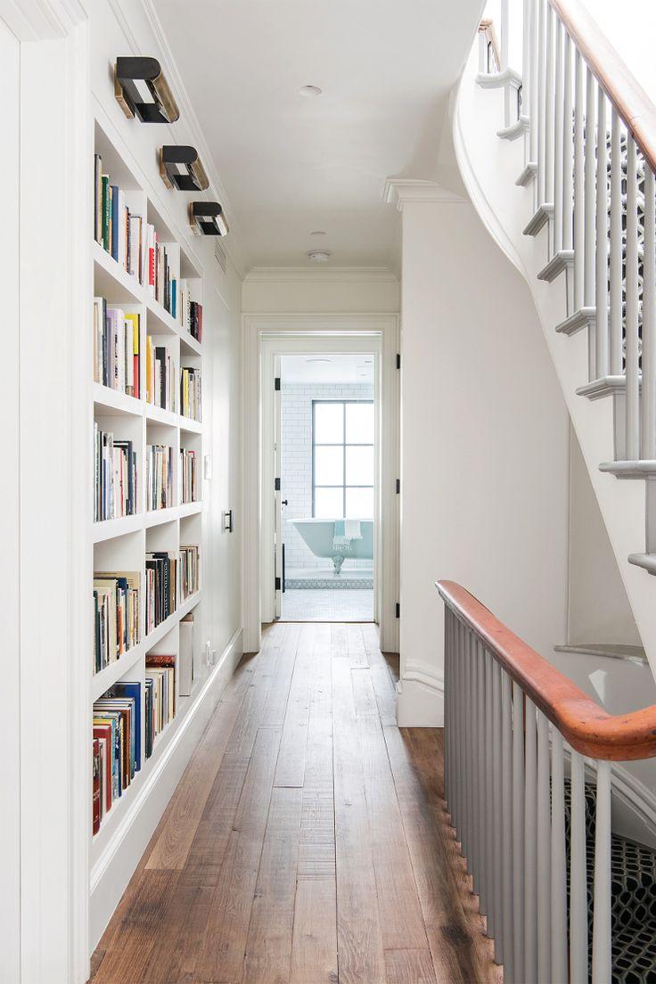 una estantera estrecha desde el suelo hasta el techo a lo largo de un pasillo