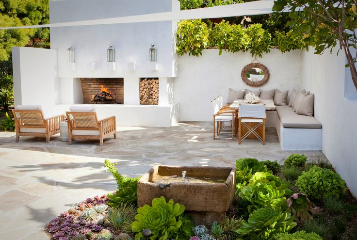 great modern organic outdoor living room with fireplace and stone fountain
