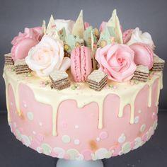 White chocolate ganache drippy cake with hand-made sugar roses and raspberry macarons.