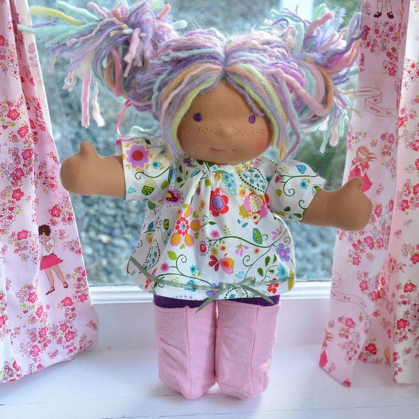 This is Joy.  She has dark tan skin, long hair made with mohair and wool yarns in a purple color with pastel rainbow fairy bits, pink and Bamboletta blue dreadlocks and purple eyes.  She is wearing the pictured outfit, underpants and wool felt shoes.
