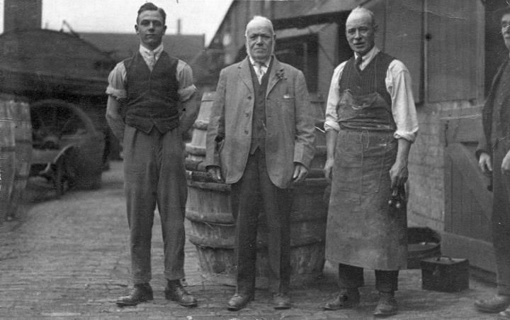 """Three generations of cooper posed outside the Middle Yard Cooperage with a union jack still in trussing hoops behind them. On the back of the photograph is written, """"Teddy, Teddy's father and grandfather""""."""