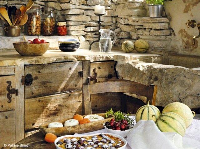 Très nature cette cuisine ouverte dispose d'un impressionnant bloc de pierre des Clarapèdes en guise d'évier, d'un plan de travail en pierre et de placards crées à partir de planches en bois. Une cuisine basée sur la récup' !