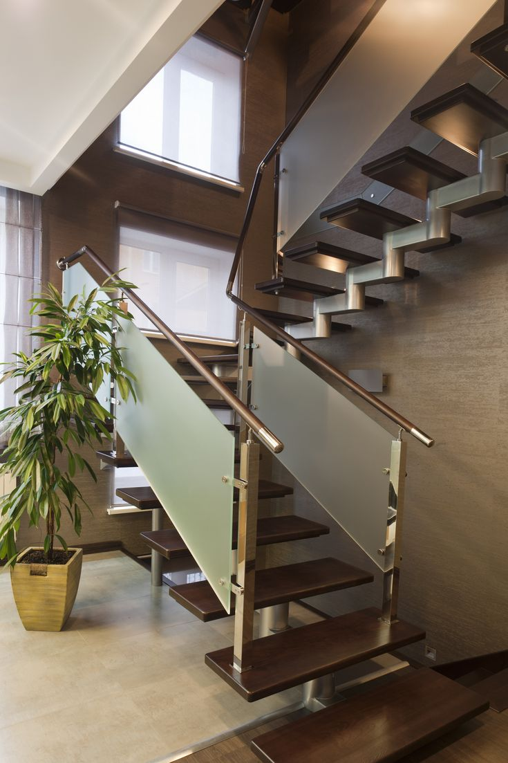 Intricate half-landing modern staircase with a single spine stringer, open risers, wood handrail with brushed glass baluster.
