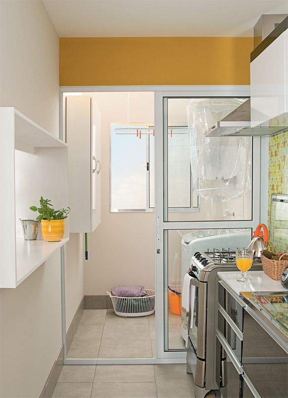Dois armários suspensos, com 22 cm de profundidade, armazenam panos e produtos de limpeza. Um deles exibe as prateleiras recortadas, perfeitas para abrigar vassouras e rodos.