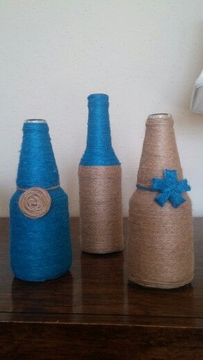 Up-cycle beer bottles by covering it up with jute and add some decoration to make it into a nice home decor