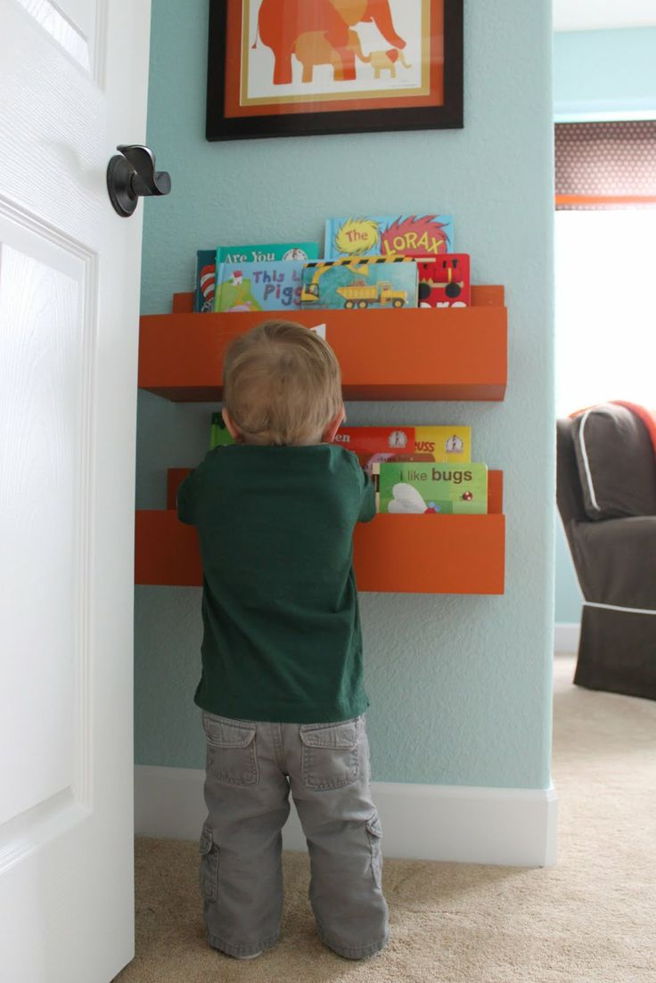 Love these orange floating shelves against a light blue wall- Macs Room