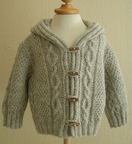 Hooded cardigan, with cables and braids.