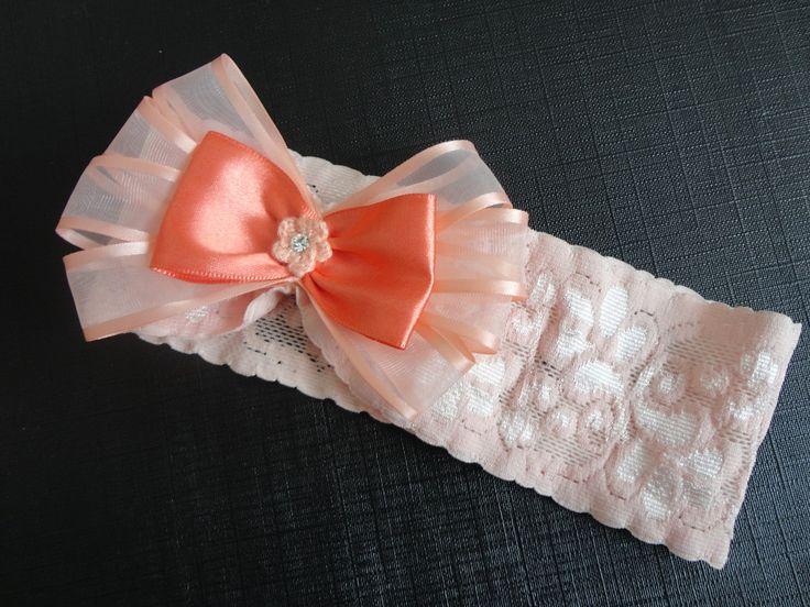 Faixa em renda larga com elastano na cor salmão claro, com laço em organza salmão claro e laço de fita salmão.