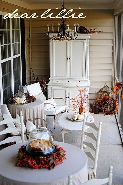 White Wooden Wall Cupboard Outdoor Dining Table Chandelier Fall Leaves Ornament And White Pumpkin Decor And Ceramic Floor
