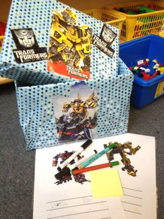 """""""Transformers"""" was used to target specific children for writing development. A Transformers box was created for interest and then filled with provision aimed at specific development. The use of the contents of the box was modelled by an adult with a writing focus."""