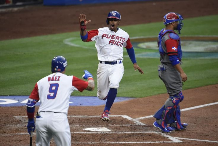 Francisco Lindor #12 of Puerto Rico, center, is congratulated by Javier Baez #9 after scoring during the first inning of World Baseball Classic Pool F Game One between the Dominican Republic and Puerto Rico at PETCO Park on March 14, 2017 in San Diego, California.