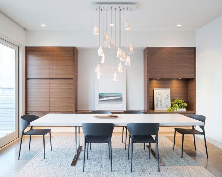 In this modern dining room, sculptural pendant lights hang from the ceiling, while built-in walnut cabinets create plenty of storage space.
