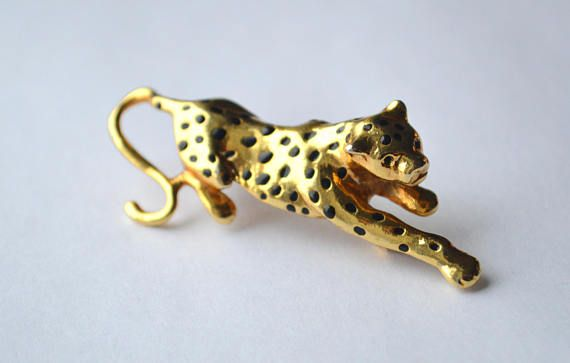A fantastic occasion to get yourself a cat, if you cant afford a real one!  A big lurking cat - looking like a leopard, a panther or a jaguar, depending on the point of view - vintage brooch. It is gold tone metal with enamel black spots. A brooch comes in a presenting box - as seen in the picture.  It measures 5.5x2 cm (2.16x10.78), its in a very good vintage condition and closes securely.  Leopards, apart from being beautiful, hypnotising and intriguing are considered very strong totems…