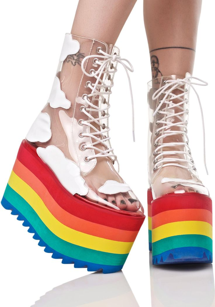 "Current Mood Happy Daze Platforms when perfectly paired with rainbow skies, makes the most uplifting vibe. These ever fabulous platforms have floated down from above with an epic clear PVC construction and white cloud accents makin' ya feel xxxtra dreamy. Featurin' the prettiest lightweight 4.5"" stacked rainbow platform with textured treads and front lace up closure cuz yer days are 'bout to get a whole lot happier."