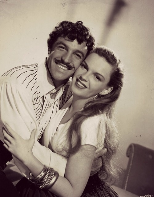 Gene Kelly & Judy Garland. A rare photo of Gene Kelly with facial hair and Judy Garland with long hair.