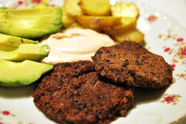 En tallrik med avokado, dressing, potatis och vegetariska biffar av svarta bönor.
