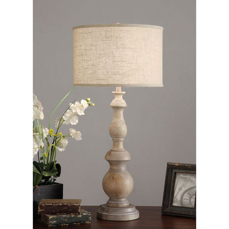 This beautiful table lamp is constructed of wood with a milky washed finish. This 1-light lamp is finished with a switch and a fabric drum shade.
