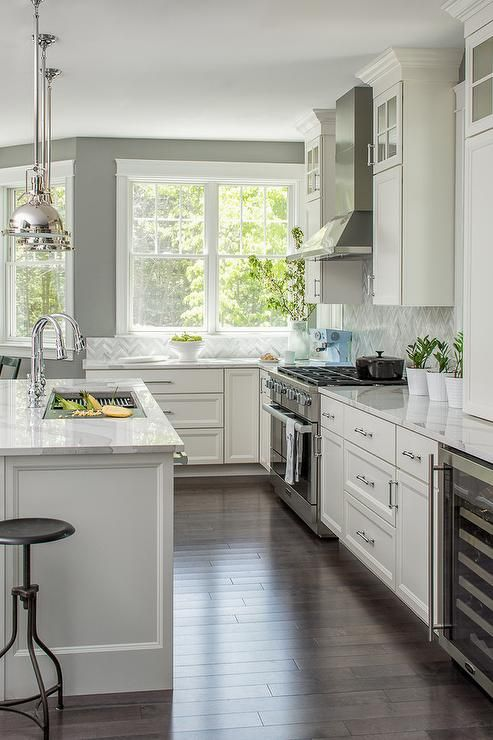 gray and white kitchen features a white kitchen island topped with a white marble countertop seating - White Kitchens
