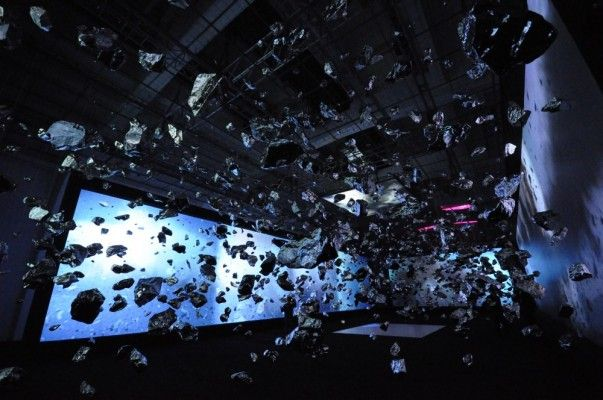 The 5,000+ pieces of stainless steel rock fragments that make up the hanging sculpture were arranged based on an actual detonation. Zhan started by recording an exploding boulder using six strategically placed high-definition video cameras, recording at 2,000 frames per second.    The recordings, which are projected onto the walls surrounding the sculpture, were meticulously studied, frame-by-frame, to determine the trajectories of the various pieces of shrapnel. With multiple camera angles to work with, Zhan was able to recreate a single moment of the explosionExplosions Installations, Cameras Angled, Videos Cameras, Steel Rocks, Bangs Theory, Big Bang Theory, Art Design, Big Bangs, Stainless Steel