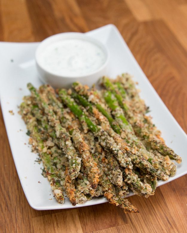 Asparagus Fries |   INGREDIENTS 1 bundle of asparagus 1 cup crushed almonds* ⅓ cup parmesan 1 tablespoon garlic powder 2 tablespoons dried oregano 1 teaspoon salt 1 teaspoon pepper 2 eggs PREPARATION 1. Preheat oven to 425°F/220°C. 2. Cut off about 1-2 inches of asparagus ends. Set aside.  3. In a large bowl combine crushed almonds, parmesan, garlic powder, oregano, salt, and pepper.  4. Dip asparagus in eggs, and then toss with the breadcrumbs 5. Bake for 15-20 minutes, flipping halfway