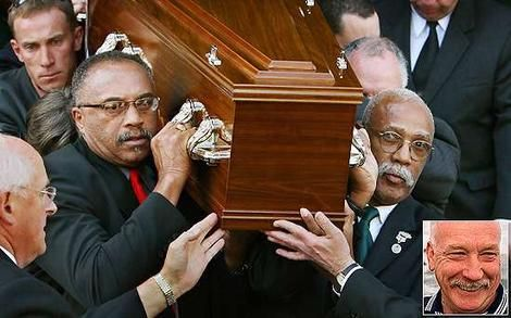 Olympic athletes Tommie Smith, left, and John Carlos carrying the coffin of Peter Norman (inset); the pallbearers were the two Americans with whom he shared the victory dais at the 1968 Mexico Olympics. The Americans were shoeless and each raised a hand in a black power salute during the American national anthem. Norman, who had run second behind Smith, stood with them wearing the badge of the Olympic Project for Human Rights.