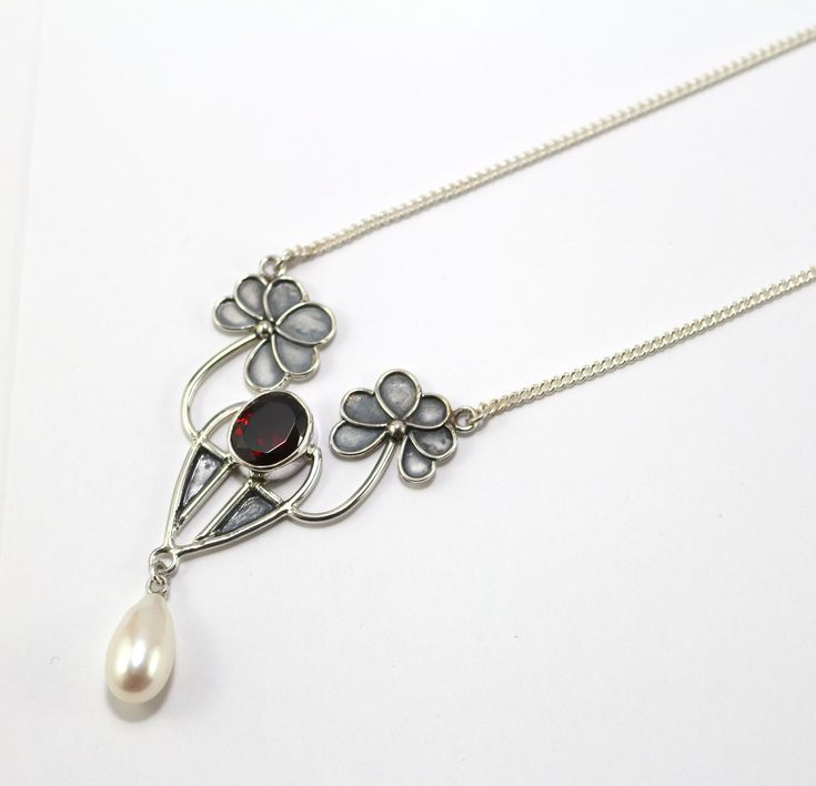 Faceted cut Garnet stone surrounded with sterling silver in an Art Nouveau/Deco design with a complemented pearl drop.  #MYC #artnouveau #artdeco #mycaravancollection #dreamsjewelleryandgifts #sterlingsilver #garnet #facetedcut #gemstone #pearldrop #pearl #necklace