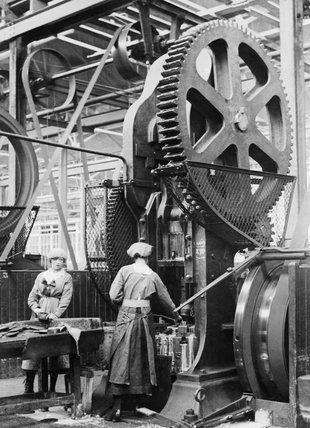 Two women munition workers operate a shell case forming machine during the First World War at the New Gun Factory of the Royal Arsenal, Woolwich, London. Lewis G P © IWM (Q 27846)