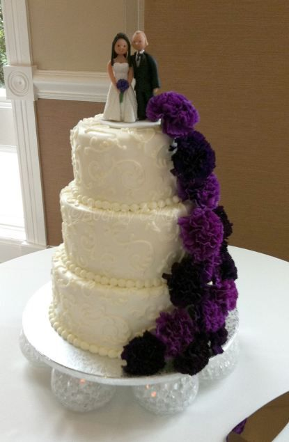 3 tier white wedding cake with bride and groom toppers and purple flowers.JPG
