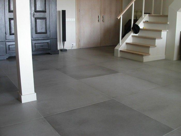 Moderne grijze stenen vloer. De grote grijze stenen tegels geven deze hal een prachtige basic uitstraling. Door de trap maar aan één kant van een leuning te voorzien, blijft het een open geheel.
