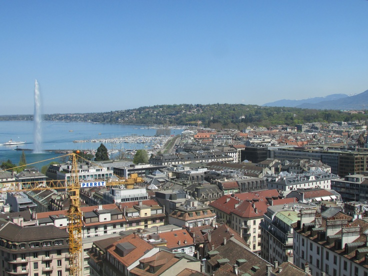 Over Geneva - This photo shows us the beautiful architecture of Geneva from above and we are shown the amazing fountain with some the mountains in the background, truly stunning
