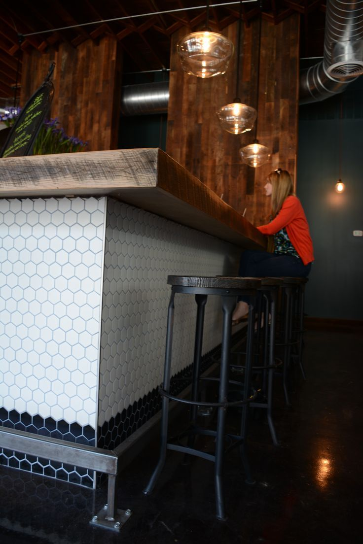 Brick and Tin reclaimed wood bar top and hex tile bar front.