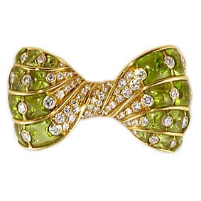 Bulgari Peridot Bow Brooch.An 18 karat yellow gold, peridot and diamond bow brooch. Stamped Bulgari. The brooch is designed as a twisted bow set with 20 pieces of polished peridot that are accented by 22 larger diamonds and centering 46 diamonds. The bow is set with a total of 68 diamonds with a total approximate weight of 2.98 carats.Circa 1980s
