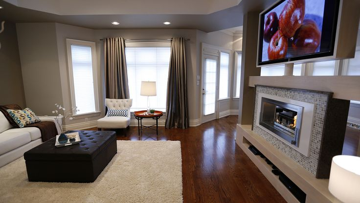 We reclaimed this formerly cramped and cluttered living space with clean high-contrast decor, a two-way fireplace, and a TV mount that swivels to allow it to be viewed from both the living and dining room.  Designed and built by Paul Lafrance Design.