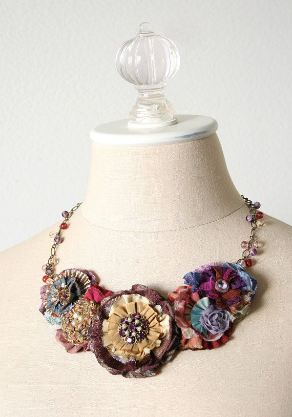 Be noticed in this eye-catching flower necklace featuring layers of hand cut and sewn fabrics in colorful jewel tones. Pretty textures and mixed