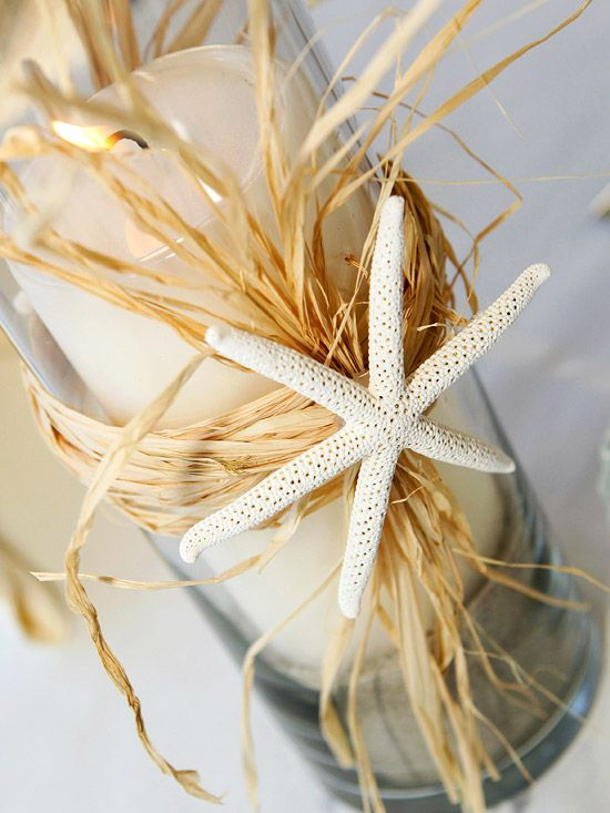 Easy-to-Make DIY centerpieces for a beach wedding. Clear glass hurricanes, tied with raffia have a starfish accent.