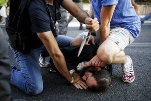 People disarm an orthodox Jewish assailant shortly after he stabbed participants at the annual gay pride parade in Jerusalem