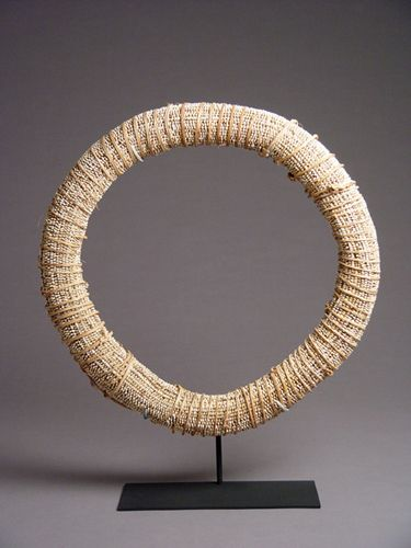 Large circular currency ring made from numerous nassa shells on a continuous thread. This elegant object is a nassa shell currency ring from the Tolai people of East New Britain, Papua New Guinea.