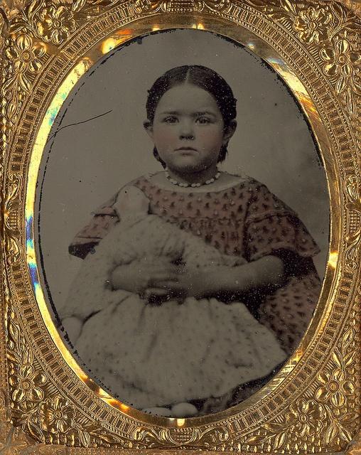 Little girl in a pink dress holding a doll. Photostudio C.B. Lawry, Farmington, Maine