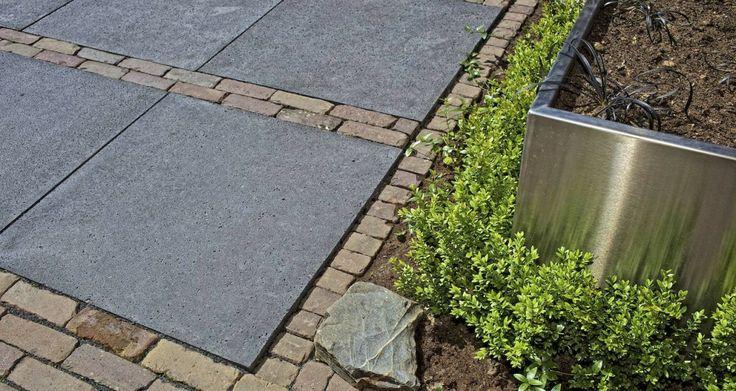 In deze tuin is een mooie combinatie gelegd van Schellevis tegels in de kleur antraciet en gebakken klinkers. Afmeting 80x80x5 cm.