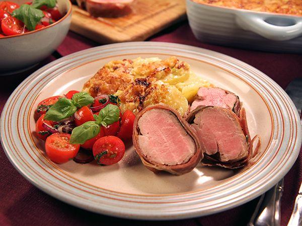 Bästa fredagsmiddagen med saftig ugnsstekt fläskfilé inlindad i parmaskinka och salvia. Servera med potatisgratäng med parmesan och enkel tomatsallad.