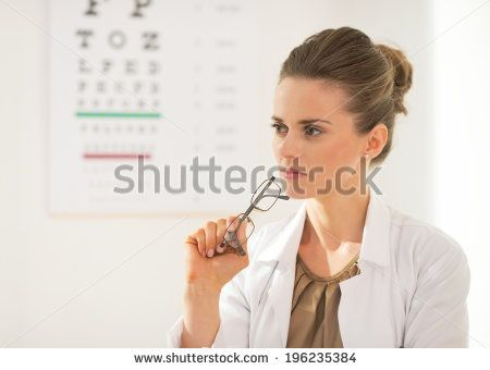 Portrait of thoughtful ophthalmologist doctor woman with eyeglasses in front of snellen chart