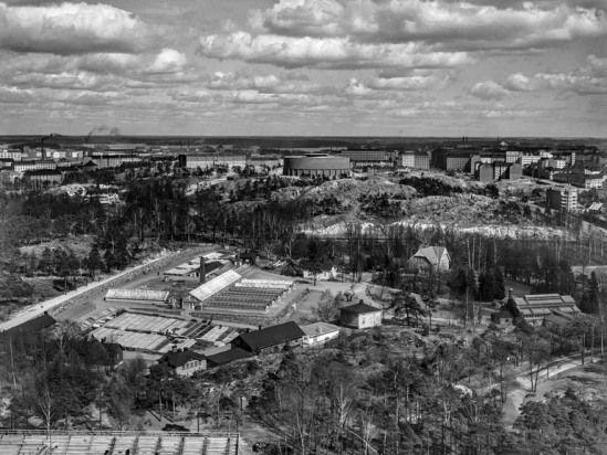 1938 - 1950 . Näkymä Stadionin tornista itään. Etualalla Kaupungin puutarhan tuotantoalue ja talvipuutarha, Hammarskjöldintie 1. Taustalla Alppila, Alppiharju ja Alppilan vesitorni nykyisen Linnanmäen alueella. Kuva hkm, R.Roos