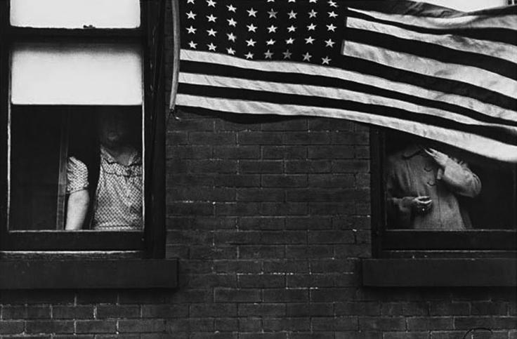 """Robert Frank    Frank esperaba hasta asegurarse que lo que veia por el visor fuera exactamente lo que quería fotografiar, esto por ejemplo ocurre en la foto donde la bandera americana tapa el rostro de un espectador  de un desfile, o en la imagen de un hombre, visto desde una ventana, que corre por una calle en direccion opuesta  a una flecha que aparece sobre él en la fachada de una casa.  SMITH se referia a él como el """"KAFKA de la fotografía"""""""