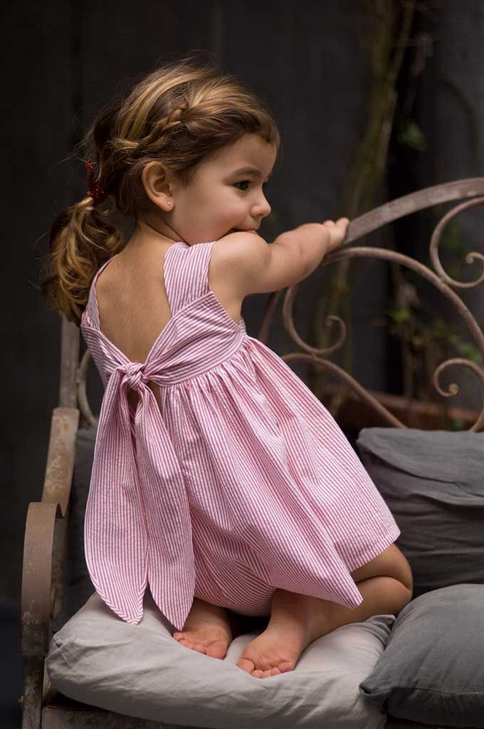 Simple and stunning. Pink low back dress with exaggerated ties. #estella #girls #fashion