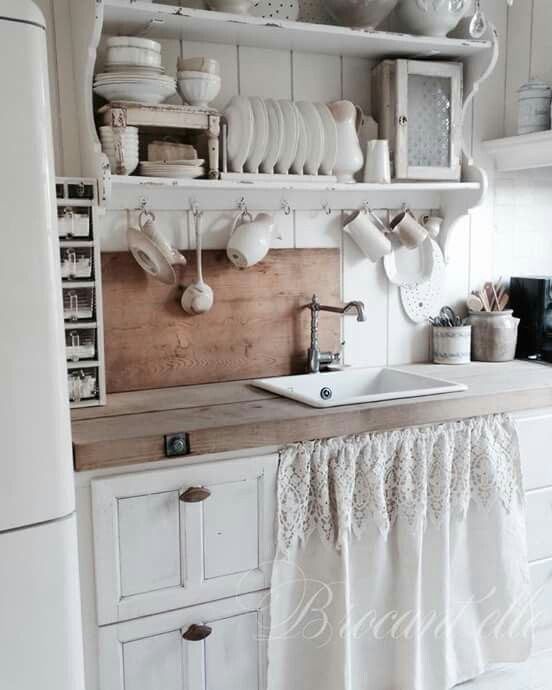 White farmhouse style kitchen. Love the curtain skirt in two fabrics! I also really like the economy of space without looking too cluttered. Nice!