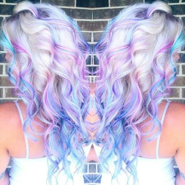 Pastel blues and purples in a bleach blonde hair color. Curly.